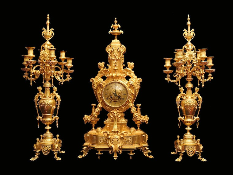 This antique gilded clock with matching gold candelabras